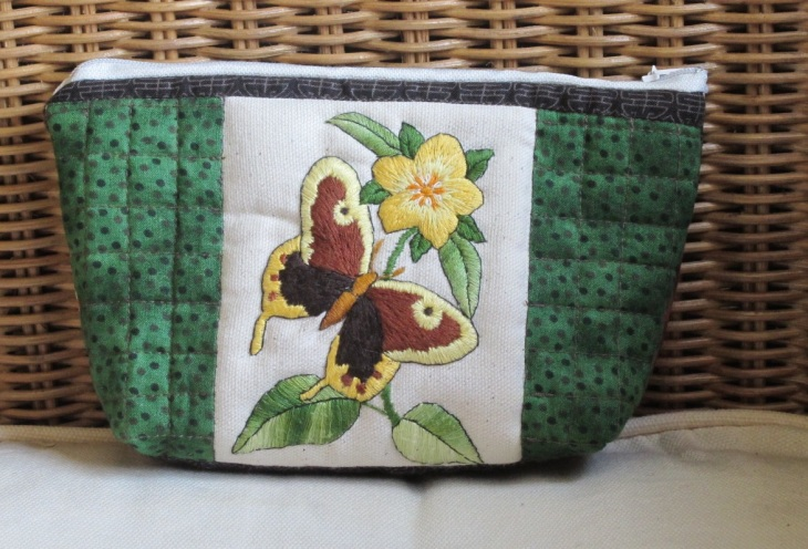 This pouch measures 7 x 5 inches (18 x 12 cm). The front shows a butterfly and flower while the back is made with a Log cabin design using fabric along the brown spectrum. Sold.