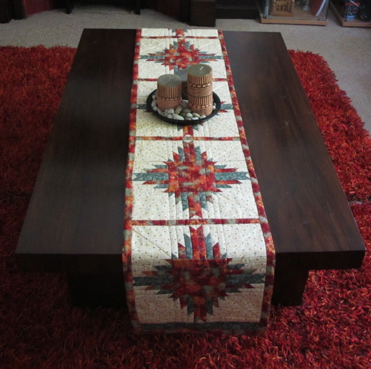 This runner is 84 x 13 inches (213 x 33 cm) and consists of 5 delectable mountains blocks. The item was designed using red and green fabrics to match the red carpet and curtains in the living room. Sold.